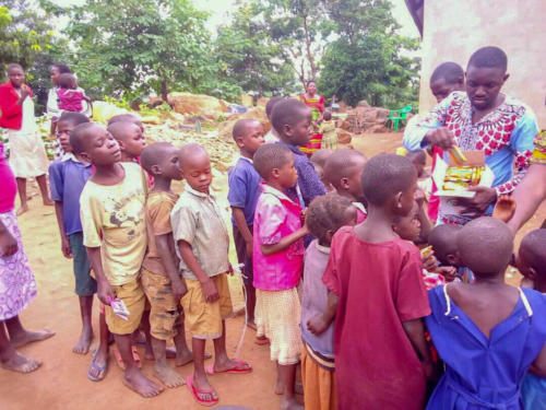 the orphans wait to be served a meal
